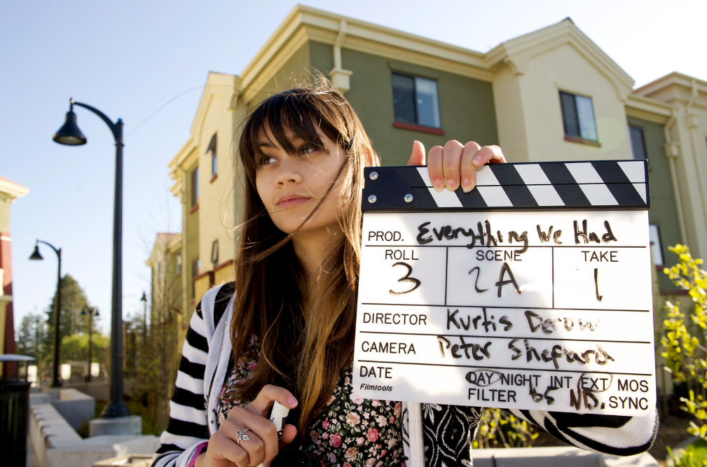A picture of a film producer holding a slate board on set